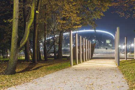 Poland, Upper silesia, sports hall, lit up at dusk, seen from the Chrobry Park, autumn