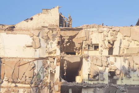 Building under demolition, sunlit, bulldozers, blue sky 版權商用圖片