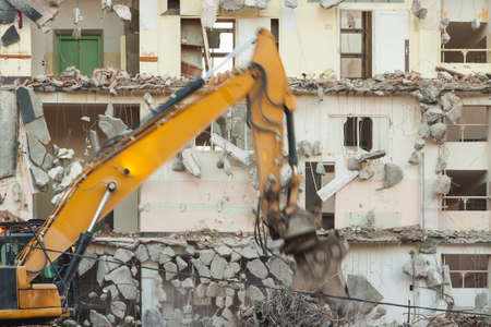 Building under demolition, motion blurred bulldozers