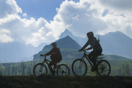 Silhouette of two cyclists against mountain landscape and overcast sky