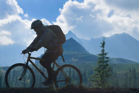 Silhouette of a cyclist against mountain landscape and overcast sky Banco de Imagens