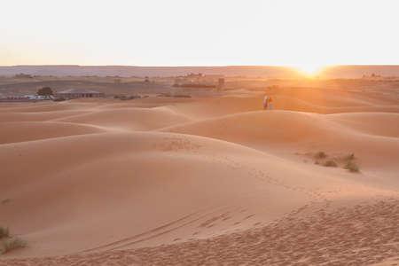 A couple watchint the sunrise at Erg Chebbi dunes at Sahara desert, Morocco Banco de Imagens