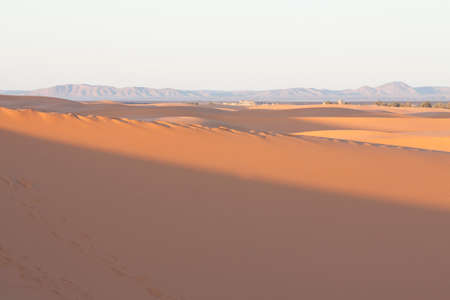 Erg Chebbi dunes at Sahara desert, Morocco, sunlit at sunrise; Anti-Atlas mountains on the horizon
