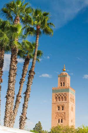 Koutubia Mosque minaret in Marrakech, Morocco, sunlit, blue sky, palm trees