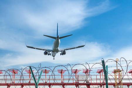 Commercial Jet Aircraft Landing, gear down, overcast sky, approach lighting system visible Standard-Bild