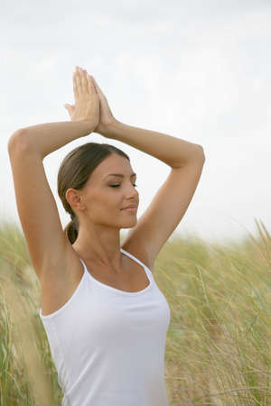 exercices: Young woman doing yoga exercices outside