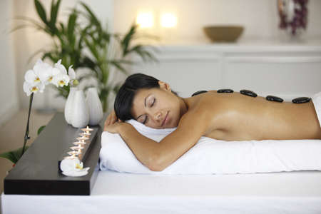 massage stones: Beautiful woman with hot stones on her back
