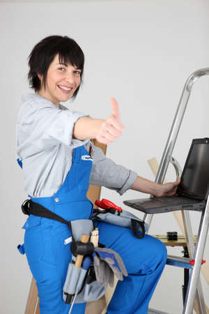 Woman carpenter with thumb up photo