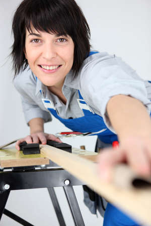 Woman carpenter working piece of wood photo