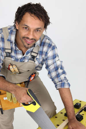 Carpenter sawing piece of wood Stock Photo - 7252720
