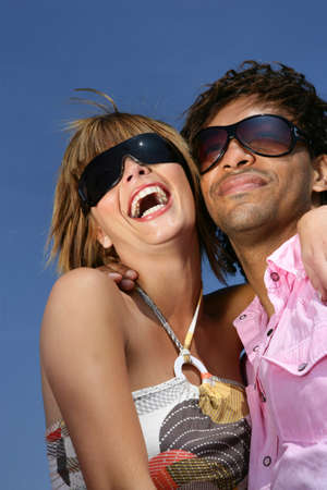 Closeup of a young couple smiling with sunglasses photo