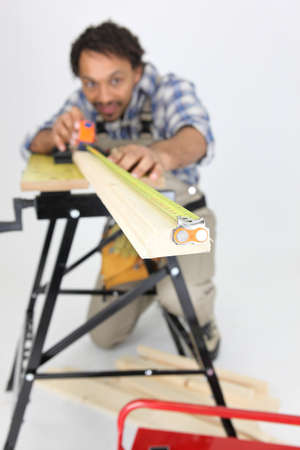 Carpenter measuring a piece of wood Stock Photo - 10548764
