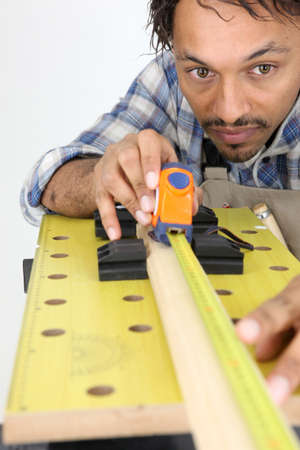 workbench: Carpenter measuring a piece of wood Stock Photo