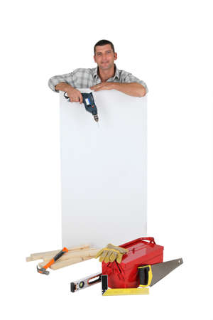 Man holding drill next to blank advertising panel photo