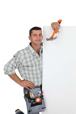30 to 35: Handyman holding a hammer and a blank sign Stock Photo