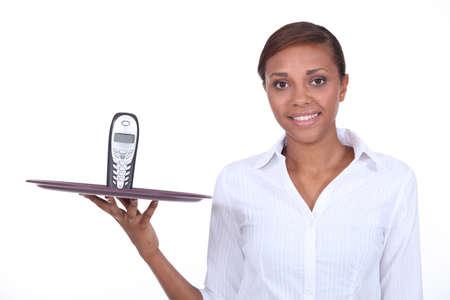 Waitress holding tray with mobile telephone on it photo