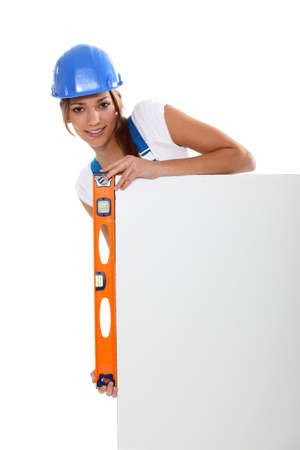 Woman checking a blank board is straight with a spirit level photo