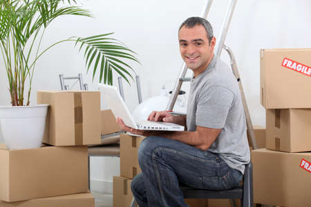 Man using a laptop computer sitting amongst cardboard boxes Stock Photo
