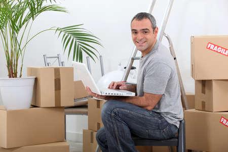 amongst: Man using a laptop computer sitting amongst cardboard boxes Stock Photo