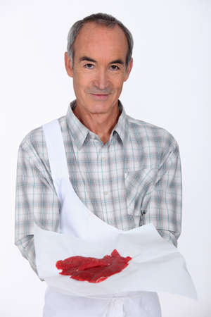 prime adult: Butcher with a piece of steak Stock Photo