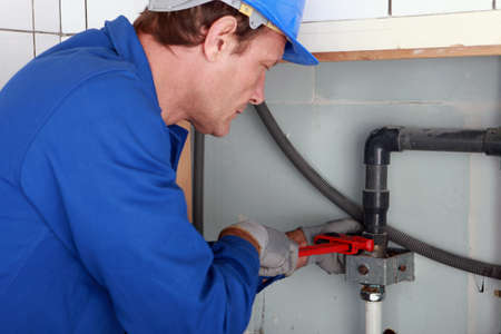 lekken: Loodgieter aandraaien van een joint met een sleutel Stockfoto