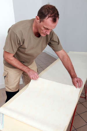 Decorator using a wallpaper table Stock Photo - 10747280