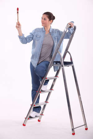 young female painter on ladder with raised brush Stock Photo - 10746756