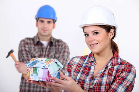 Builders with a house made of money Stock Photo - 10747206