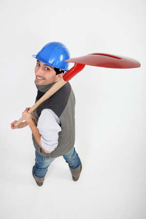 Laborer carrying shovel on white background photo