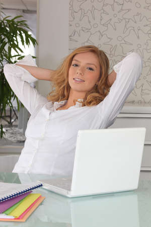 Young woman at a laptop with her arms stretched behind her head Stock Photo - 10747207