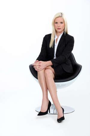 mujeres sentadas: Disparo de estudio de una rubia empresaria en un traje