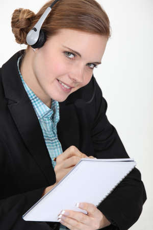 Receptionist writing in a notebook Stock Photo - 10746743