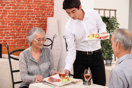 dining out: Senior couple being served food in a restaurant