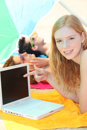 microcomputer: pretty girl pointing her laptop while her friends are tanning