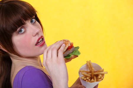 beefburger: Woman eating burger and chips Stock Photo