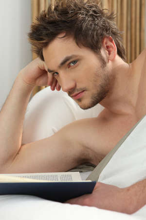 Young man reading in bed Stock Photo - 10746830