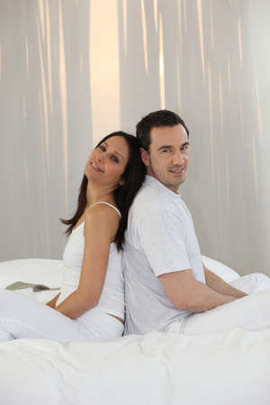 Couple sitting back to back on a bed Stock Photo - 10747255