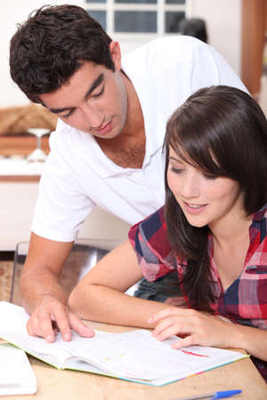 Young couple looking at a magazine at home Stock Photo - 10747236