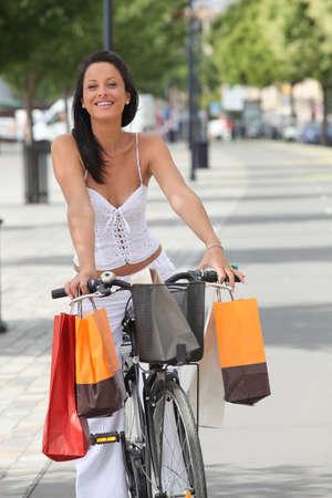 Donna con borse per la spesa del ciclismo Archivio Fotografico