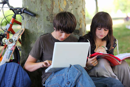 coursework: Young students doing their homework in a park