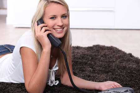 Female teen lying on a brown rug chatting on the telephone Stock Photo - 10746778