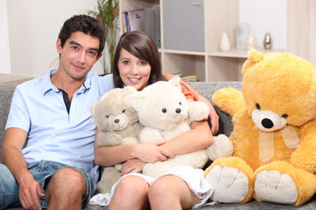strangeness: Couple sat on couch with cuddly toys