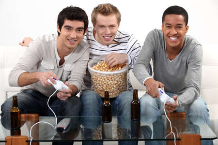 Three friends playing video games while drinking beer. photo