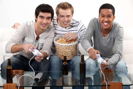 jugando videojuegos: Tres amigos jugando videojuegos mientras bebía cerveza. Foto de archivo