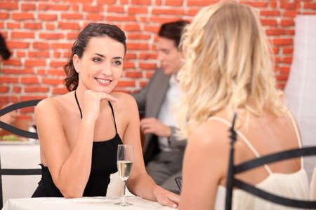 lesbienne: deux filles vêtues de robes de parler dans un restaurant