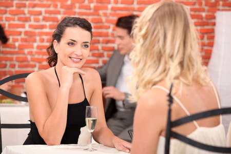two girls dressed in robes talking in a restaurant Stock Photo - 10746793