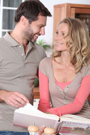 Couple with a cookbook Stock Photo - 10747386