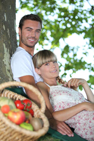 Couple sat by tree with basket of fresh produce photo