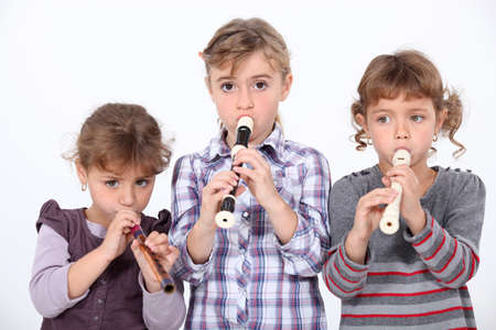 Three young girls playing the recorder Stock Photo - 10747356