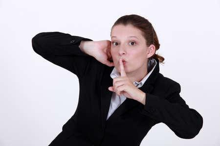 stifle: Businesswoman shushing Stock Photo